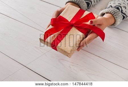 Woman's hands give wrapped christmas or other holiday handmade present in paper with red ribbon. Present box, decoration of gift on white wooden table