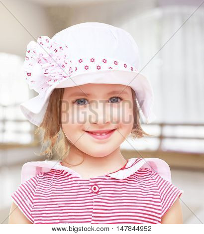 Portrait of beautiful little blond girl in a white hat with a pink bow. Close-up.On the background of the hall with a large arched window , the concept of learning and child development.