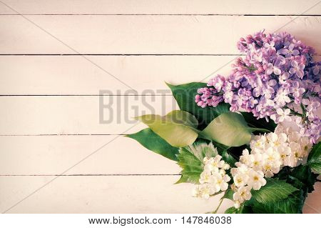 Lilac flowers and white flowers with green leaves on vintage white/yellow wooden background. Copy space for text. Great use for gift cards, post cards, invitation cards and posters.