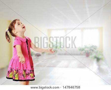 Adorable little girl with pigtails on the head , in a pink dress. The girl was looking at the top turned sideways to the camera.Against the background of a large room with Windows and flowers .