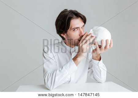 Young brunette man kissing fake skull and looking at camera isolated on the gray background