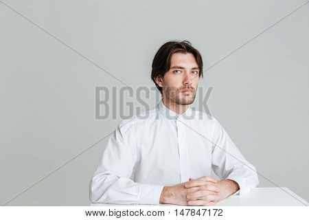 Pensive calm brunette man in white shirt sitting at the table and looking at camera isolated on the gray background