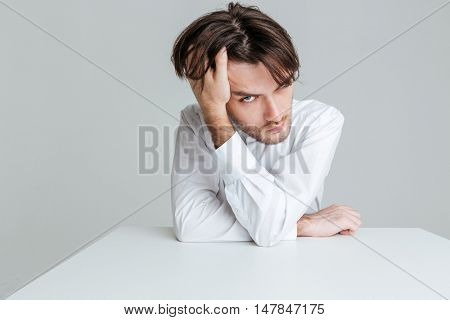 Close up portrait of a pensive young brunette man in white shirt sitting at the table isolated on the gray background
