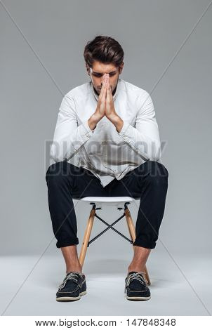 Concentrated handsome young man white shirt praying with closed eyes isolated on a gray background