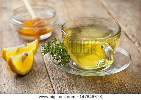 thyme tea in glass cup sprig of fresh thyme lemon slices honey on the old wooden background