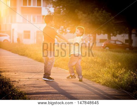 Two boys playing together on street with sun back light, toned image