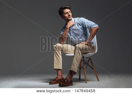 Attractive young brunette man in blue shirt sitting on the chair and looking away over grey background