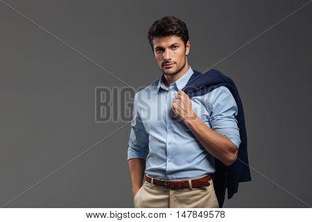 Handsome businessman holding his jacket over shoulder on gray background
