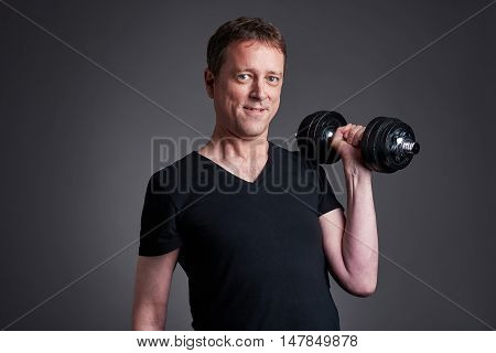 A middle age man standing and lifting weights.