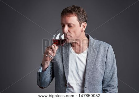 A middle age man holding and smelling a glass of wine