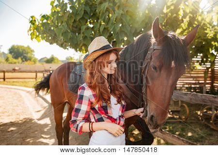 Beautiful redhead young woman cowgirl standing and taking care of her horse in village