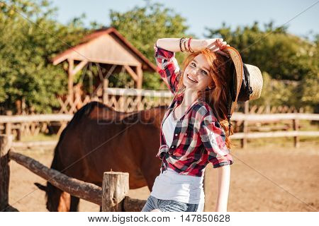 Happy charming young woman cowgirl with horse on ranch