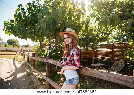 Cheerful pretty young woman cowgirl walking on farm