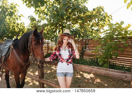 Cute redhead young woman cowgirl walking with her horse in village