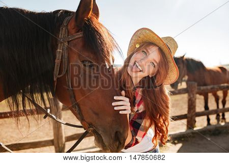 Cheerful playful young woman cowgirl standing with horse and showing tongue