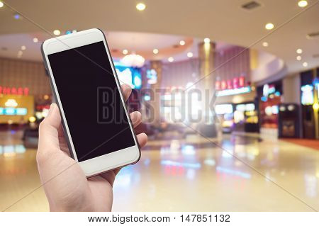 Human Holding Mobile Phone with blank screen on Department store blurred background