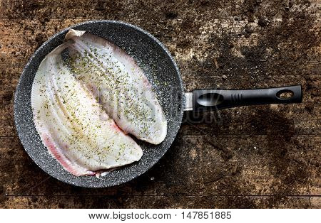 high-angle shot of a pair of raw flounders dressed with herbs in a frying pan, placed on a rustic wooden table