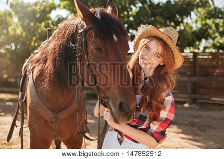 Portrait of smiling pretty young woman cowgirl in hat with her horse