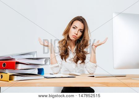 Young confused beautiful businesswoman shrugging shoulders over white background