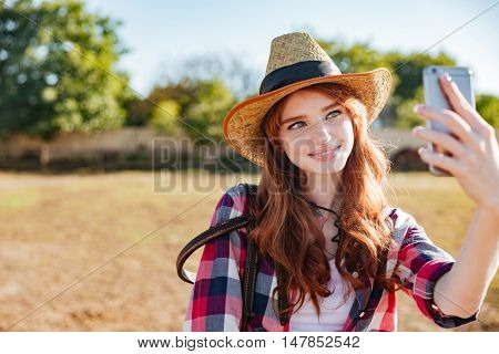 Smiling attractive young woman cowgirl taking selfie with mobile phone on ranch