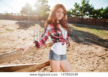 Smiling beautiful young woman cowgirl standing on ranch