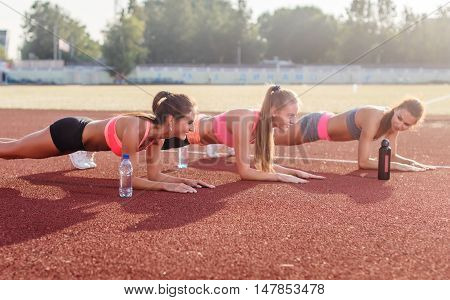 Athletic group of women training on a sunny day doing planking exercise in the stadium