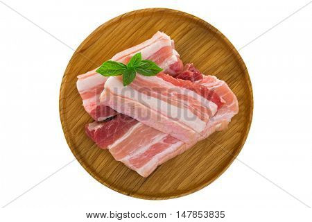 Slices of raw fresh pork belly cut on wooden plate isolated on white background