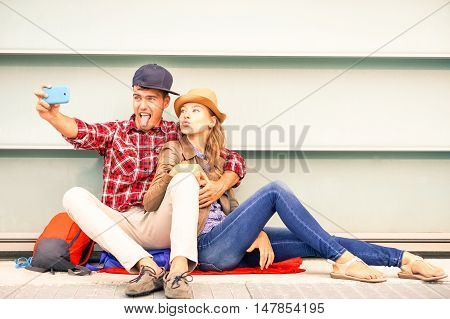 Young couple taking selfie doing funny faces outdoors sitting on the street - Teenagers having fun using new mobile photo camera and relaxing - Urban concept of friends joyful moment after school day