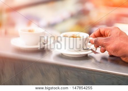 Man drinking coffee cup at bar counter - Male hand holding espresso at cafe shop - Concept of caffeine addiction and people daily habits -