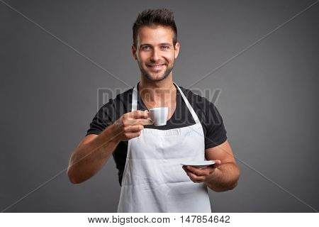 A young barista man smiling and enjoying a cup of coffee