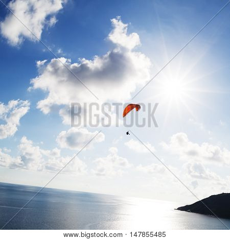 Paraglider flying over the water