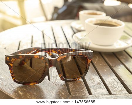 Sunglasses and coffee cup on wood table in the coffee shop under sunlight in the morning with warm / soft color tone (Selective focus)