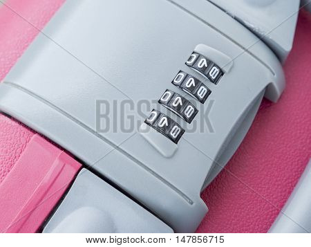 Closeup zipper lock password number on pink suitcase