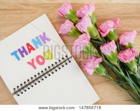 Font Thank you on blank notebook and bouquet of Carnation flower with wood background on top view