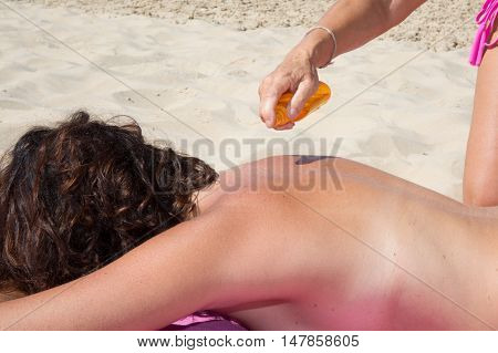 Attractive Woman Lying At Beach With Sun Protection Cream