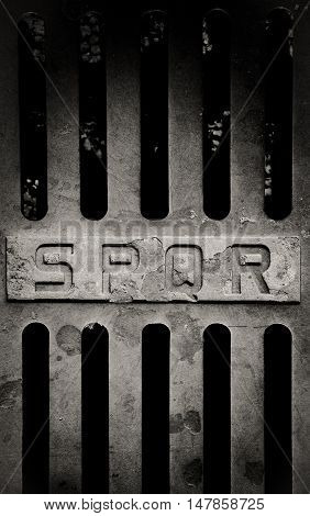 Iron old roman manhole cover detail with spqr sign