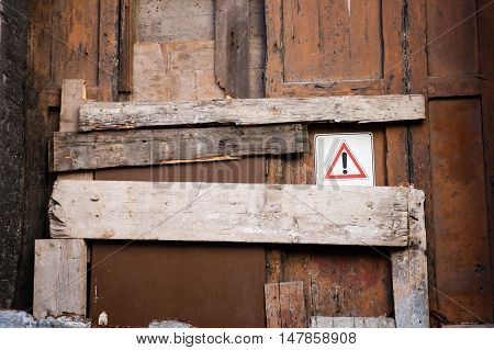 Warning symbol on old ruined door closed and blocked with wooden plank