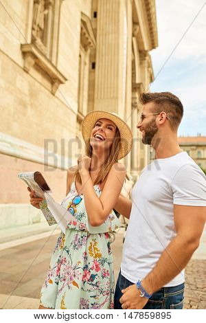 A beautiful young couple are standing and laughing at the St. Stephens Basilica in Budapest, Hungary.