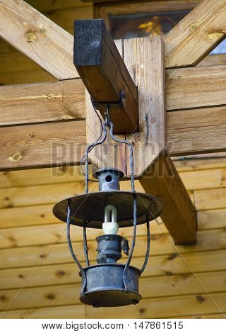 an old lamp in the rafters of a wooden bar-shaped house