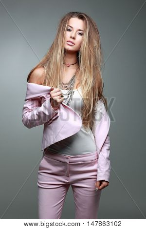 A photo of beautiful girl is in fashion style on  grey  background, glamour