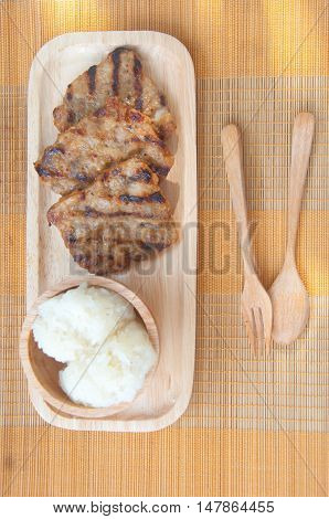 Grilled pork and sticky rice Thai style food on mat
