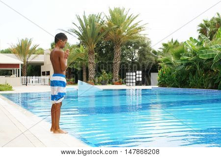 Boy preparing to jump into swimming pool.