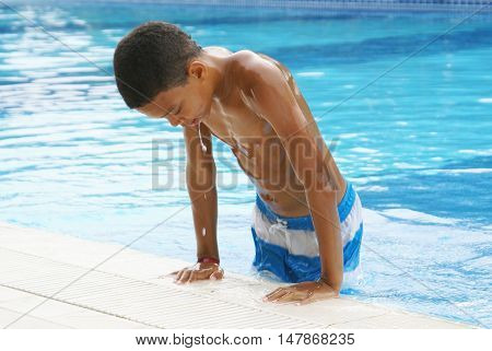 Boy leaving swimming pool. Hot summer day.