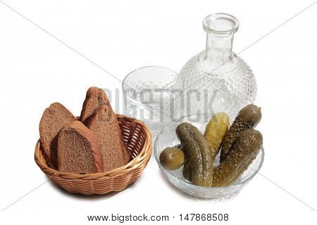 Vodka in glass and pickled cucumber on a white background