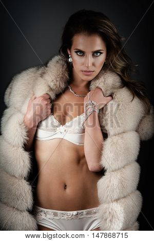 Beautiful lady in sexy lingerie poses in fur coat