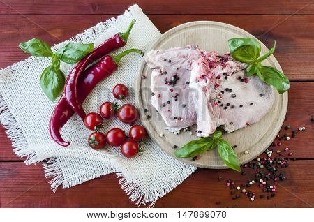 raw pork steak with spices and vegetables