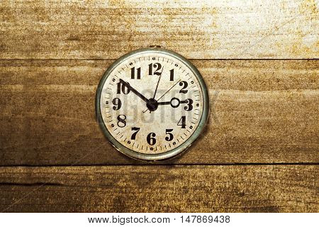 Time work and business concept. Old clock on wooden background. Grunge picture.