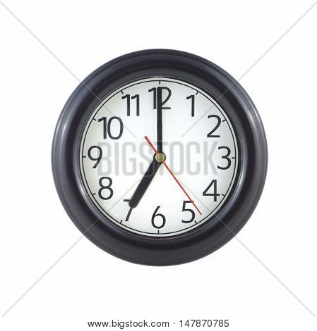 Big round wall clock with a dark rim on white background closeup and arrows showing seven o'clock