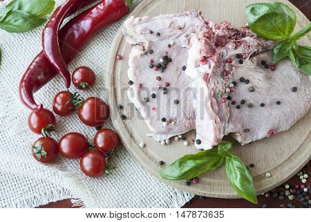 raw pork steak with vegetables and basil