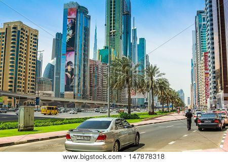 Dubai, United Arab Emirates - May 1, 2013: street view of Sheikh Zayed Road in Dubai Downtown with its modern skyscrapers and towers with billboards. Dubai financial district skyline.